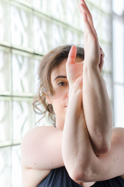 A bright and lively image of a woman doing yoga with arms crossed and gazing intently outward