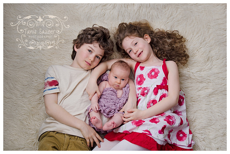 A beautiful image of three siblings cuddling close during their family photography session with Tanis Saucier Photography.