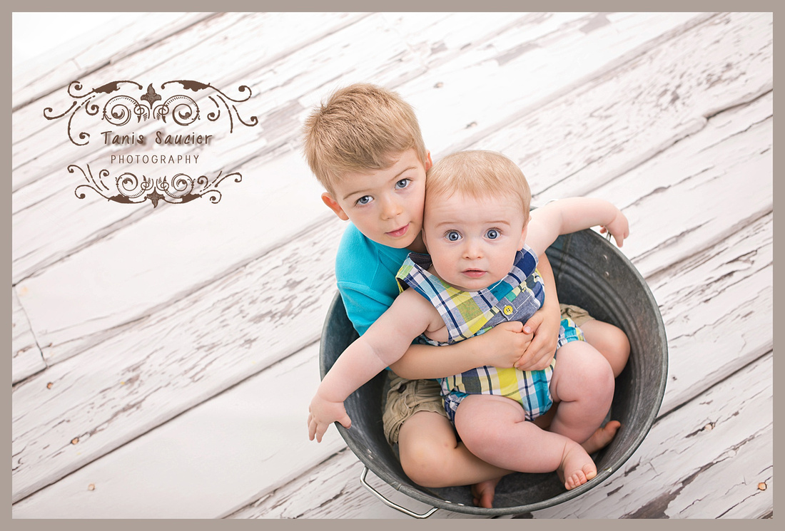 A pair of brothers sit together in a wash bin while looking up into the camera during their children's portrait session in Montreal