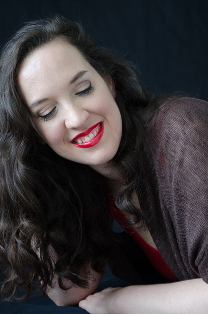 A close up image of a beautiful woman, smiling while looking down, wearing a brown sweater and daring red lips