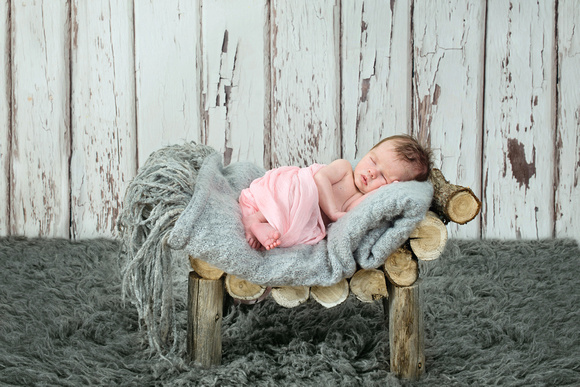 A newborn baby girl sleeping on a rustic wooden bench by Tanis Saucier Photography