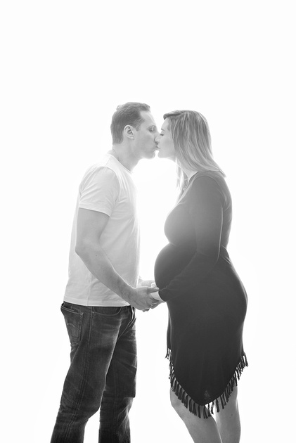 A black and white image of a couple kissing with stunning back lighting during their maternity portrait session in Montreal.