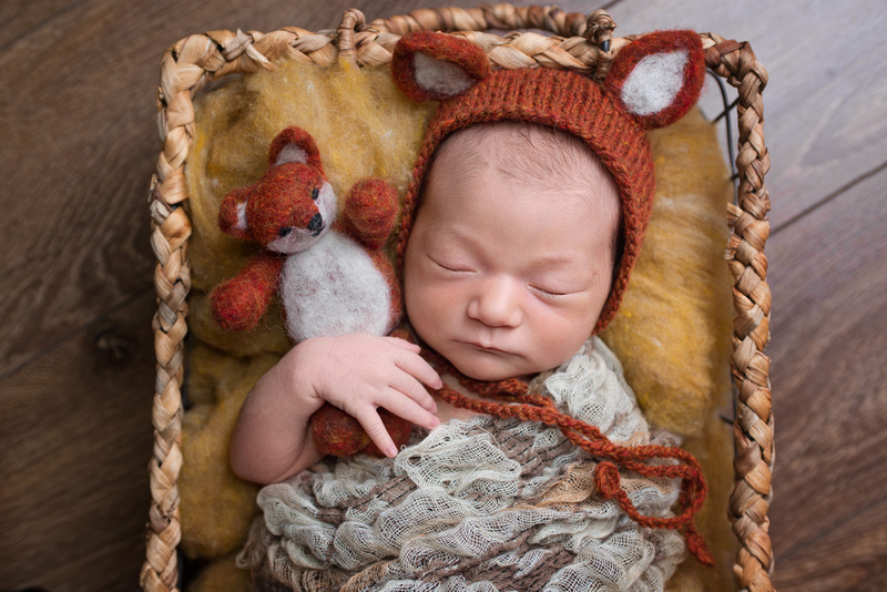 A sweet image of a little newborn girl wearing a fox hat during her newborn photography session with Tanis Saucier in Montreal