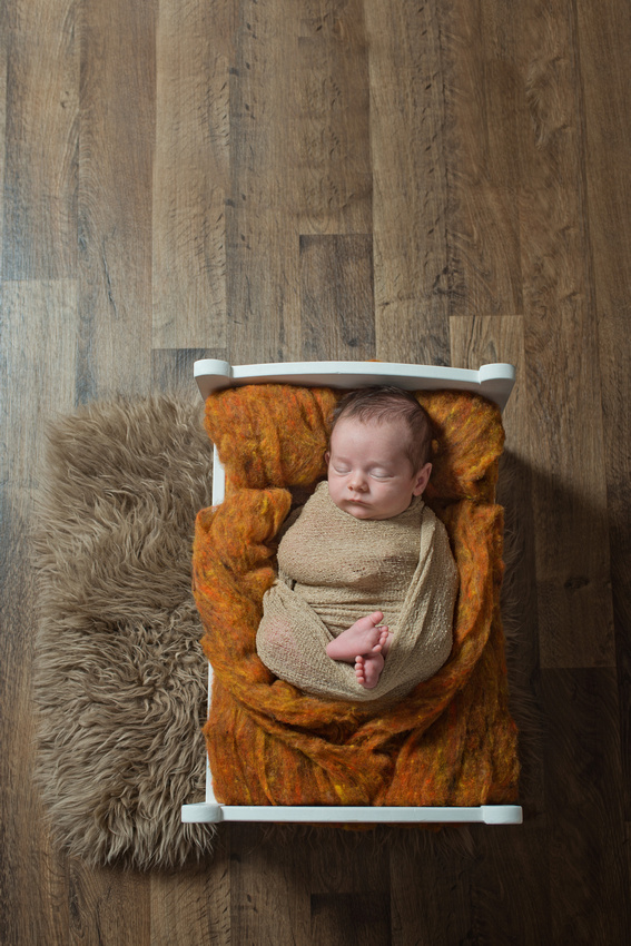 A sweet 4 weeks new baby boy sleeping in a tiny bed during his new-born photo session with Tanis Saucier Photography