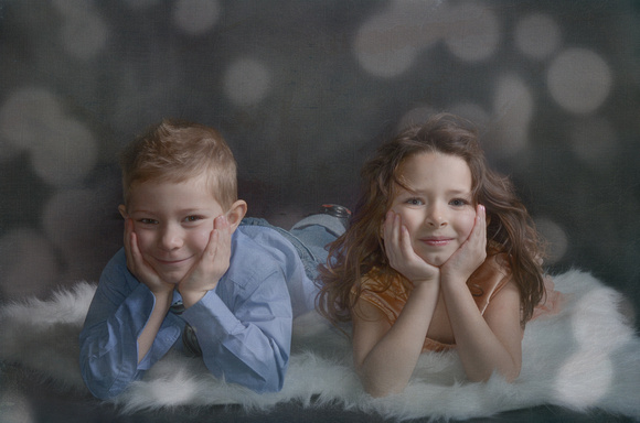 A sweet artistically textured image of a brother and sister lying on a white fur with their faces in their hands
