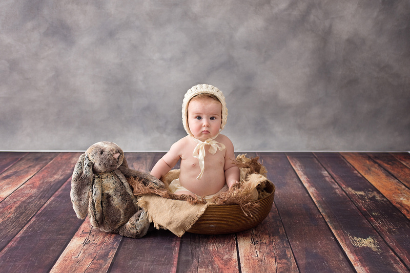 A beautiful little girl sits in a basket with her lop-eared bunny stuffy during her milestone photo session with Tanis Saucier Photography in Montreal
