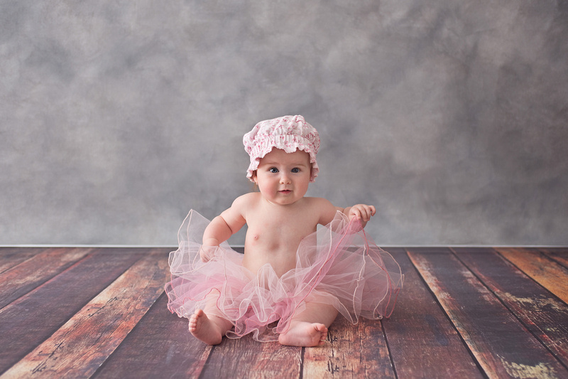 A beautiful little girl sits in a pink tutu and milk maid bonnet during her milestone photo session with Tanis Saucier Photography in Montreal