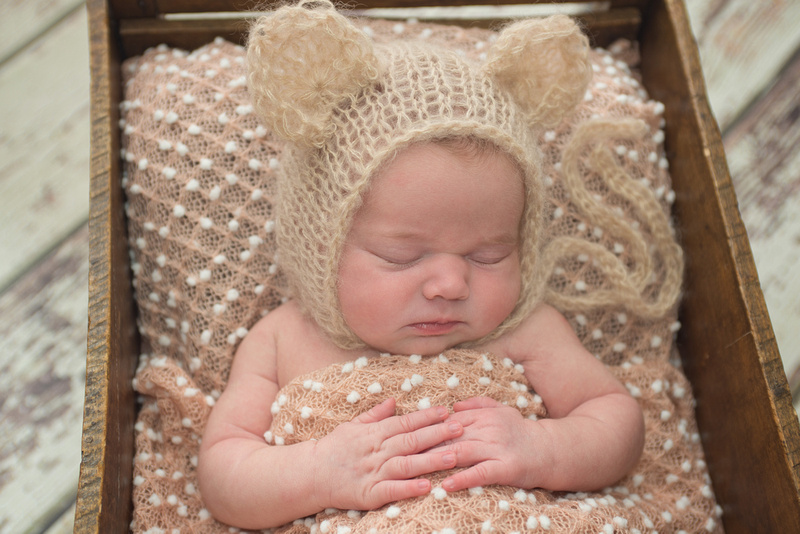 A newborn baby girl wearing a bear bonnet is nestled in a little crate during her newborn photography session with Tanis Saucier Photography in Montreal