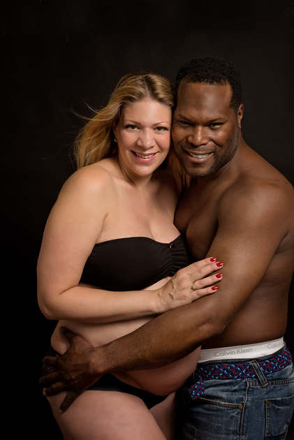 A beautiful mixed couple are captured in a sweet embrace during their maternity photography session with Tanis Saucier Photography in Montreal