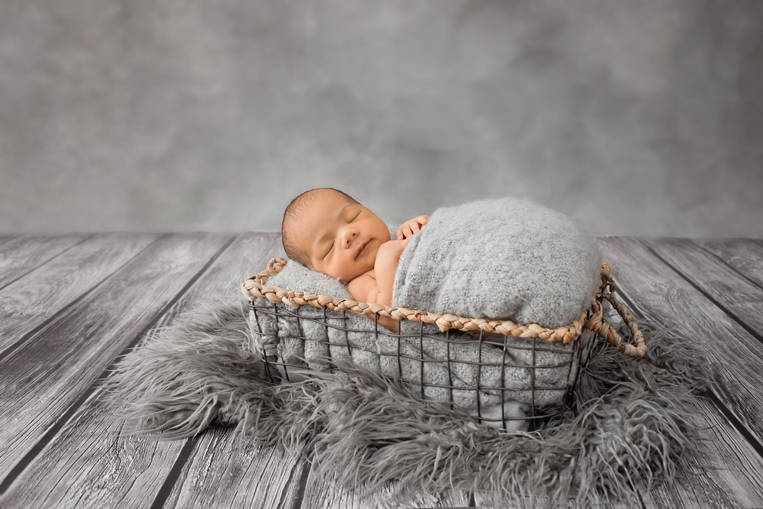 A side view of a newborn baby boy sleeping in a basket prop with grey fur and blanket during his newborn photography session in Montreal