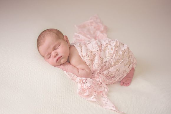 A newborn baby girl sleeps peacefully during her newborn photography session with Tanis Saucier Photography in Montreal