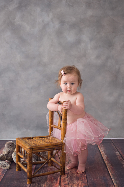 A beautiful little girl standing while holding onto a cute little chair during her milestone photo session with Tanis Saucier Photography in Montreal