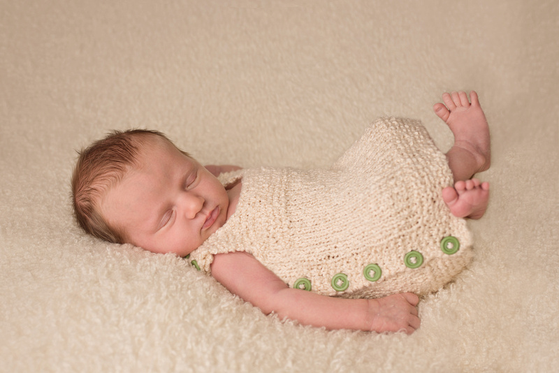 Newborn baby girl, sleeping peacefully on a soft blanket and wearing the sweetest knitted dress during her newborn photography session in Montreal with Tanis Saucier Photography.