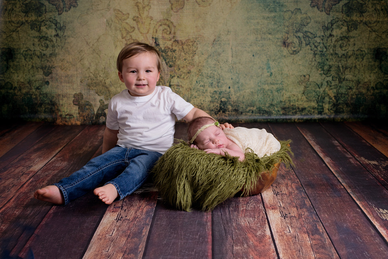 A sweet image of a big brother sitting with his newborn baby sister during her newborn portrait session with Tanis Saucier Photography.