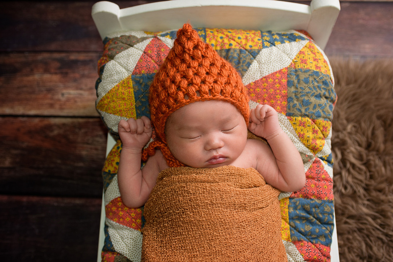 Top View Close-Up of Newborn Baby Boy Wearing a Tuque in a Bed with a Quilt