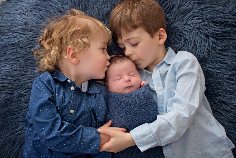 Brothers kissing newborn baby boy on head on blue flokati