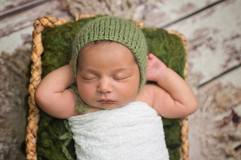 a sweet image of a newborn baby girl lying in a basket with her hands under her head wearing a green bonnet during her newborn portrait session with Tanis Saucier Photography in Montreal, Quebec. http://www.tanissaucier.com