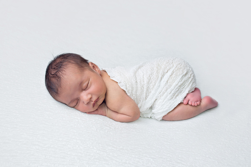 A beautiful and simple image of a newborn baby girl sleeps in the bum up pose wearing a white wrap on a white background during his newborn session with Tanis Saucier Photography in Montreal, Quebec