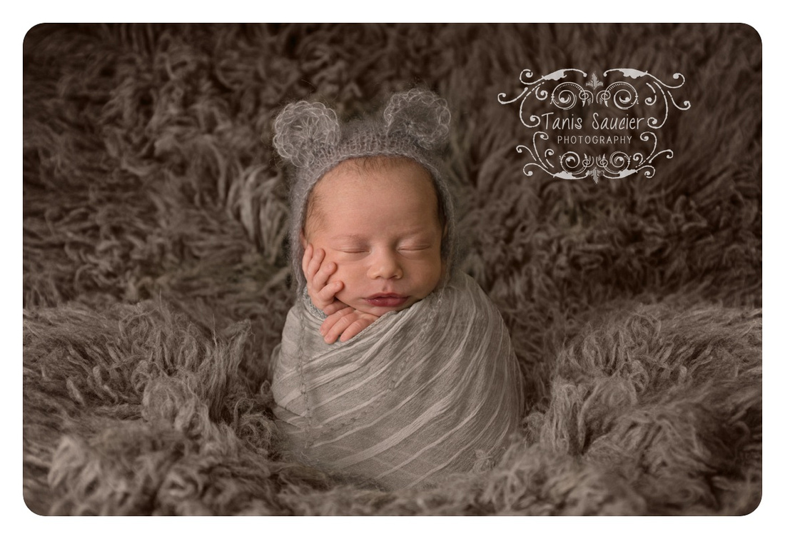 Newborn baby boy wearing a mouse-eared knitted bonnet and wrapped in grey on grey Flokati rug. #montrealnewbornphotographer #montrealnewborninfantphotography #tanissaucierphotography