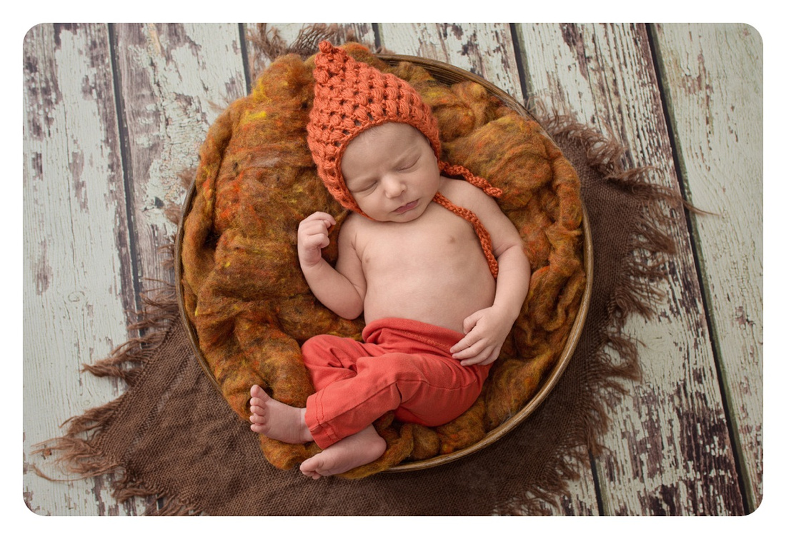 sweet-newborn-boy-in-an-orange-pant-and-bonnet