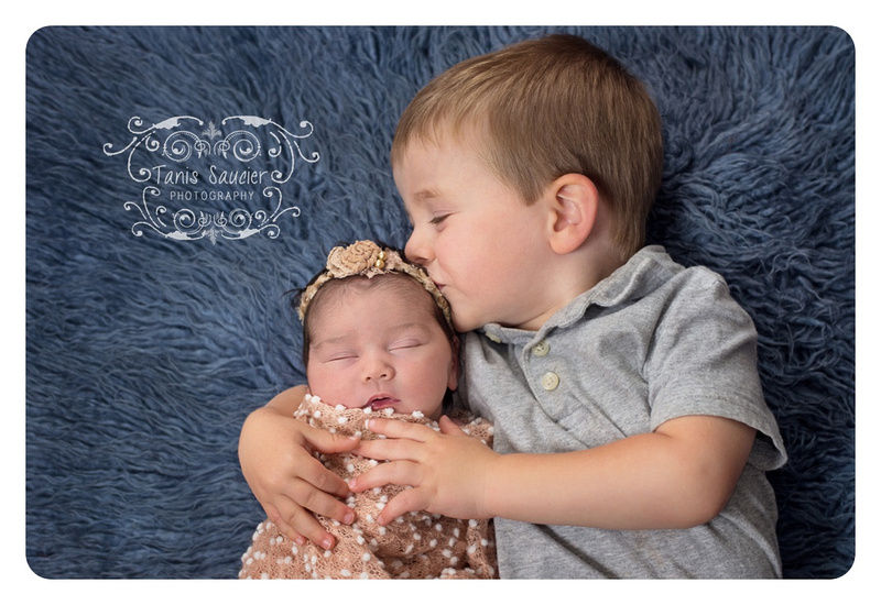 big-brother-kisses-and-snuggles-with-newborn-sister-on-blue-flokati