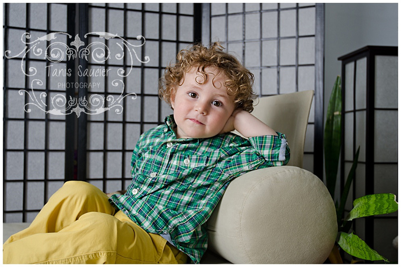 An image of a beautiful young boy posing on a couch.