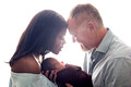 A beautiful back-lit image of a mom and dad with their newborn son during their newborn portrait session with Tanis Saucier Photography in Montreal.