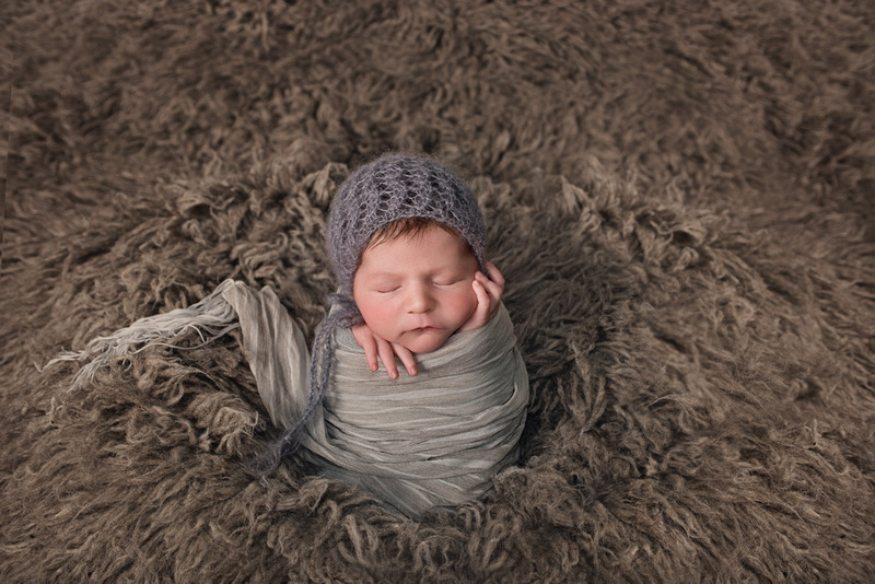a gorgeous image of a newborn baby boy in the potato sack pose on a grey flokati rug wearing a grey wrap and bonnet during his newborn portrait session with Tanis Saucier Photography in Montreal, Quebec. http://www.tanissaucier.com