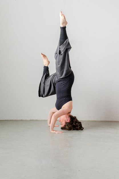 An image of a woman performing a head stand, showing strength and poise
