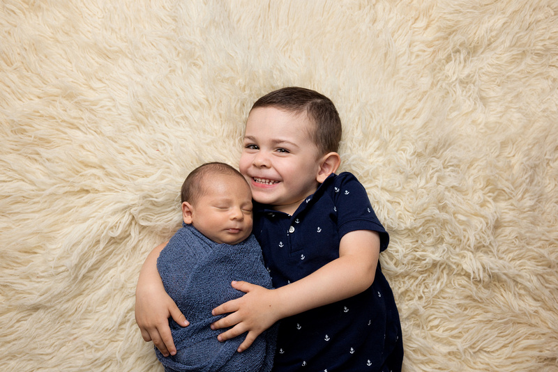 a 4 year old boy snuggles with his newborn baby brother as they lie together on a flokati rug during the newborn photography session with Tanis Saucier in Saint-Sauveur, Quebed
