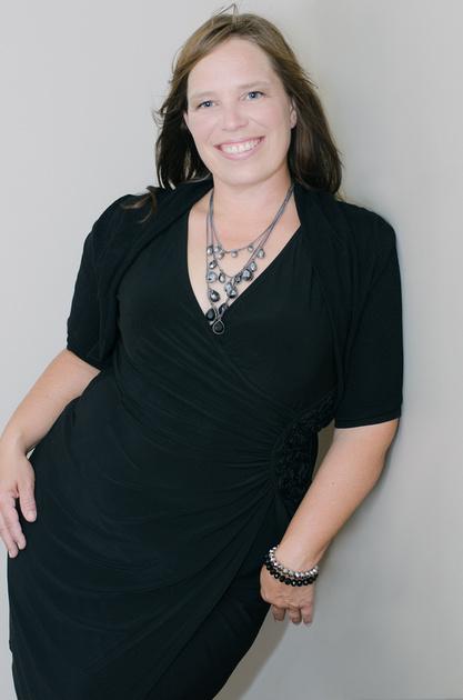 A beautiful, full length image of a curvy woman wearing a little black dress.