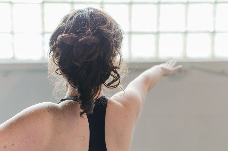 A lovely, airy image of a woman's back with arms extending outward toward a glass paned window, during her yoga photo session with Tanis Saucier photography