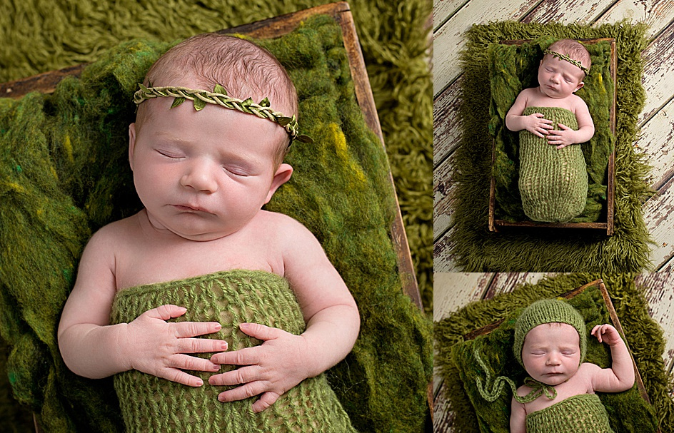 a newborn baby girl dressed in a dark green knit wrap and wearing a leaf headband is posed on her back in a wood crate lined with soft green mossy fluff.