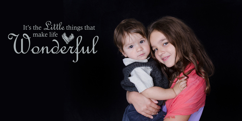 A big sister hold her little brother close as they snuggle up for a picture in their home portrait session