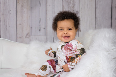 An adorable 6 month old baby girl wearing a rose romper smiles a toothless grin during her Milestone Photography Session with Tanis Saucier Photography in montreal quebec