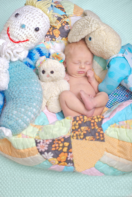 A portrait of a newborn baby surrounded by her parents' childhood toys during her photo session with Tanis Saucier Photography