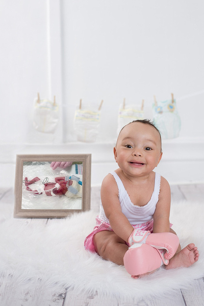 an inspirational image of a one year old baby girl wearing pink boxing gloves and matching boxer shorts while sitting beside her preemie newborn picture during her milestone portrait session in montre