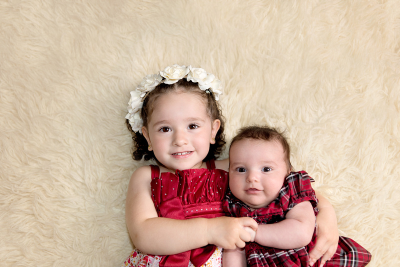 An adorable image of a 2 year old sister and her 3 month old newborn sister cuddling together in festive red outfits during the newborn portrait session with Tanis Saucier Photography in Montreal.