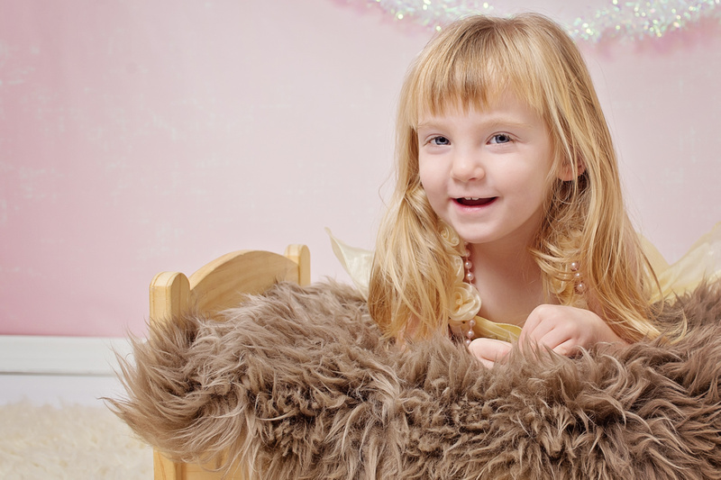 A little girl leaning on a fur covered doll bed with a yellow dress and pearls