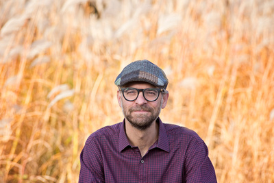 an image of a man wearing glasses and a hat in an outdoor fall family session in Saint Sauveur, Quebec with Tanis Saucier Photography.