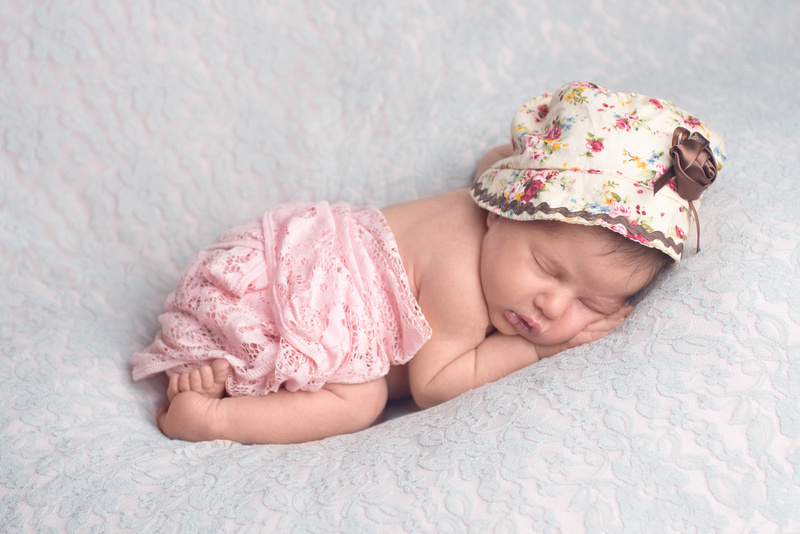 A beautiful new-born baby girl sleeping in a curled up pose during her newborn photography session in Montreal