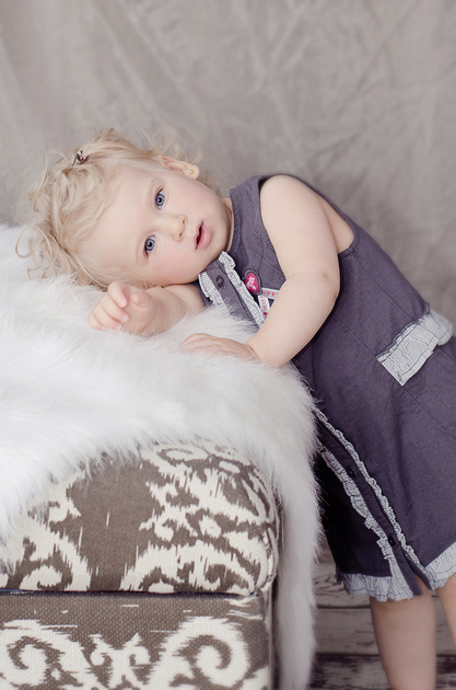 A lovely image of a blond toddler resting her head on a bear rug