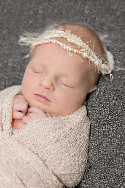 An image of a sleeping, swaddled newborn girl in Montreal during her newborn photo session