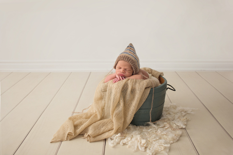 """Newborn photography session highlighting the """"head on hands"""" pose in a prop bucket at Tanis Saucier Photography's studio in Montreal."""