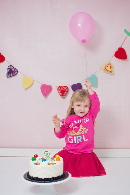 A lovely image of a 3-year old girl holding a pink balloon with a cake in front of her for her cake smash photo session with Tanis Saucier Photography