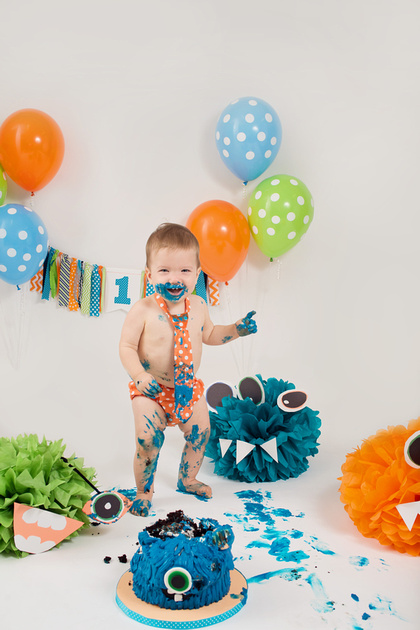A colourful set up with orange, green and blue 'monster-themed' cake, banner and paper puff monsters during this boys 1-year cake smash photo session with Tanis Saucier Photography in Montreal.