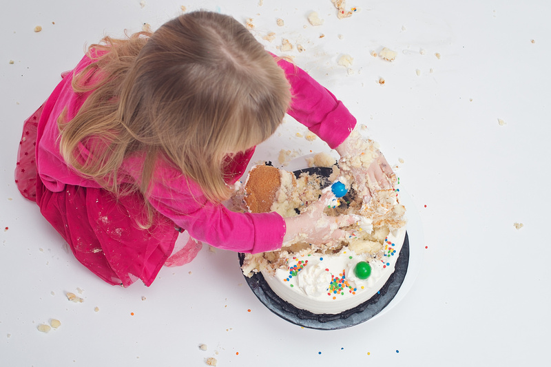 A bird's eye view of a little girl smashing a birthday cake during her cake smash photo session with Tanis Saucier Photography