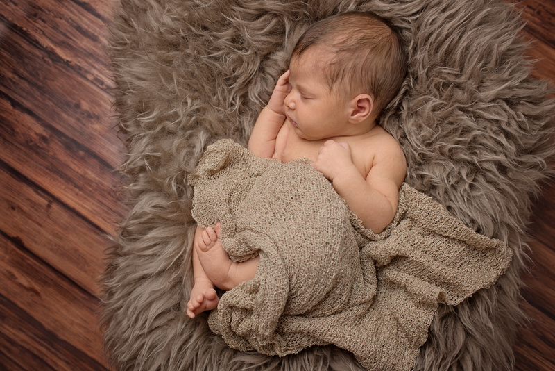 A newborn baby girl sleeping in a cozy brown fur bed with Tanis Saucier Photography