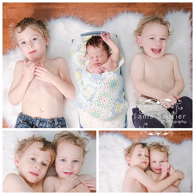 A sweet image of two brothers lying on a fluffy white fur rug with their 9 day old baby sister sleeping between them