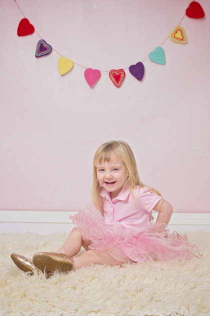 A lovely image of a little girl sitting on a fur rug wearing a pink tutu and gold shoes during her photo session with Tanis Saucier in Montreal